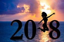 Szczęśliwa nowy rok karta 2018 Sylwetka młoda kobieta na plaży jako część liczby 2018 znak Obrazy Stock