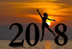 Szczęśliwa nowy rok karta 2018 Sylwetki młodej kobiety doskakiwanie na tropikalnej plaży nad morzem i 2018 liczbach z zmierzchu t Obraz Royalty Free