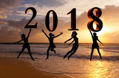 Szczęśliwa nowy rok karta 2018 Sylwetki młodej kobiety doskakiwanie na tropikalnej plaży nad morzem i 2018 liczbach z zmierzchu t Zdjęcia Royalty Free