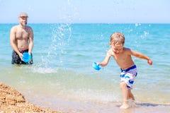 Szczęśliwa ojca chełbotania woda na roześmianym synu Fotografia Stock
