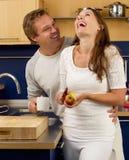 Szczęśliwa para śmia się w kuchni Obrazy Royalty Free