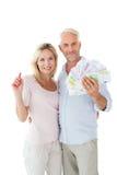 Szczęśliwa para błyśnie ich gotówkę Obrazy Royalty Free