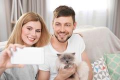 Szczęśliwa para bierze fotografię z kotem zdjęcie royalty free