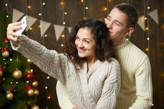 Szczęśliwa para bierze selfie i ma zabawę w boże narodzenie dekoraci Ciemny drewniany wnętrze z światłami Romantyczny wieczór i m Obrazy Stock