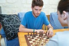 Szczęśliwa para cieszy się bawić się chesscouple bawić się szachy Fotografia Stock