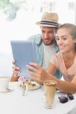 Szczęśliwa para cieszy się kawę używać pastylkę Zdjęcia Royalty Free