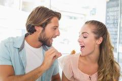 Szczęśliwa para cieszy się niektóre tortowych Fotografia Stock