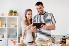 Szczęśliwa para gotuje jedzenie w domu z pastylka komputerem osobistym Fotografia Royalty Free
