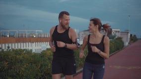 Szczęśliwa para jogging wpólnie w wieczór czasie w miasto terenie, gawędzenie zbiory