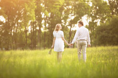 Szczęśliwa para - kobieta w ciąży i jej mąż iść na pinkinie trawa Obrazy Royalty Free