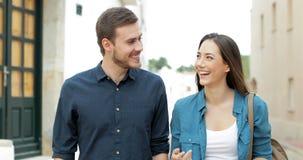 Szczęśliwa para lub przyjaciele opowiada chodzić w ulicie zbiory wideo