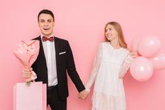 Szczęśliwa para, mężczyzna i kobieta, z bukietem kwiaty i torby w ich rękach po robić zakupy, na różowym tle _ fotografia stock
