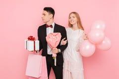 Szczęśliwa para, mężczyzna i kobieta, z prezentem i bukietem kwiaty, z torbami, po robić zakupy, na różowym tle zdjęcia royalty free