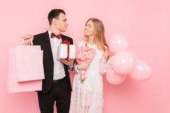 Szczęśliwa para, mężczyzna i kobieta, z prezentem i bukietem kwiaty, z torbami, po robić zakupy, na różowym tle obraz stock