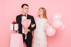 Szczęśliwa para, mężczyzna i kobieta, z prezentem i bukietem kwiaty, z torbami, po robić zakupy, na różowym tle zdjęcie royalty free