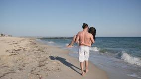Szczęśliwa para, mężczyzna mienia kobieta, wesoło przyjaciele na romantycznym spacerze lato, młodzi ludzie na pięknej plaży, face zbiory wideo