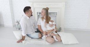 Szczęśliwa para małżeńska z córki obsiadaniem blisko białego całowania i graby troszkę zbiory wideo