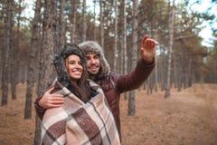 Szczęśliwa para ma odpoczynek w lesie facet ściska dziewczyny i wskazuje rękę odległość zdjęcie stock
