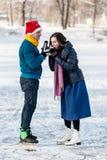 Szczęśliwa para ma zabawę i pije gorącej herbaty na lodowisku outdoors Obrazy Stock