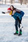 Szczęśliwa para ma zabawy jazda na łyżwach na lodowisku outdoors zdjęcia stock