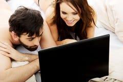 Szczęśliwa para na laptopie w sypialni Fotografia Royalty Free