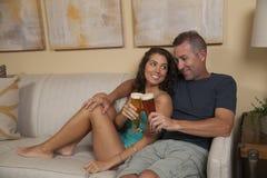 Szczęśliwa para na leżance cieszy się zimnego piwo Obrazy Stock