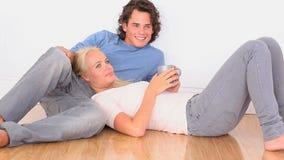 Szczęśliwa para na podłoga z filiżanką zbiory wideo