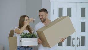 Szczęśliwa para ogląda ich nowego dom excited Młoda kobieta daje kluczom jej chłopak i całować on zbiory