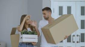 Szczęśliwa para ogląda ich nowego dom excited Młoda kobieta daje kluczom jej chłopak i całować on zdjęcie wideo