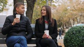 Szczęśliwa para opowiada na miasto ławce na ulicie z papierowymi szkłami w rękach zdjęcie wideo