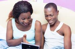Szczęśliwa para patrzeje fotografię w łóżku fotografia royalty free