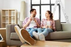 Szczęśliwa para pije kawowego chodzenie nowy dom zdjęcia stock