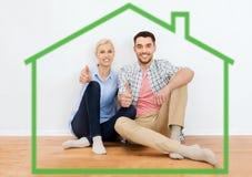 Szczęśliwa para pokazuje aprobaty przy nowym domem Zdjęcie Royalty Free