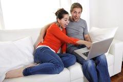 Szczęśliwa para pracuje na ich laptopie na kanapie Zdjęcia Stock