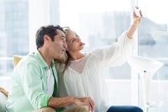 Szczęśliwa para robi twarzy podczas gdy brać selfie Zdjęcia Stock