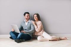 Szczęśliwa para robi zakupy online na laptopie podczas gdy siedzący podłoga zdjęcie royalty free