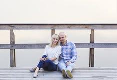 Szczęśliwa para siedzi wpólnie na rzecznym jetty mgła Zmierzch Zdjęcie Royalty Free