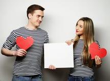 Szczęśliwa para trzyma białych pustych i czerwonych serca Obrazy Royalty Free