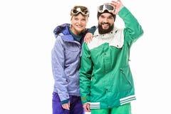 Szczęśliwa para w jazda na snowboardzie kostiumach Fotografia Stock