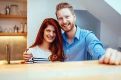 Szczęśliwa para w kuchenny ono uśmiecha się Zdjęcia Royalty Free