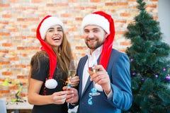 Szczęśliwa para w miłości w Bożenarodzeniowych kapeluszach ma zabawę na zamazanym tle Domowy nowego roku pojęcie fotografia stock