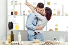 Szczęśliwa para w miłości kulinarnym cieście i całowanie w kuchni Obrazy Stock