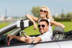 Szczęśliwa para w samochodzie bierze selfie z smartphone Zdjęcie Stock