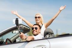 Szczęśliwa para w samochodzie bierze selfie z smartphone Obrazy Stock