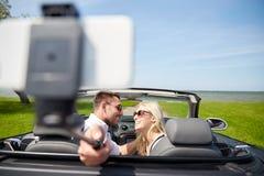Szczęśliwa para w samochodzie bierze selfie z smartphone Zdjęcia Royalty Free