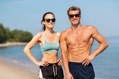 Szczęśliwa para w sportach odziewa i cienie na plaży Obrazy Stock