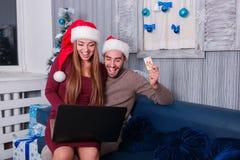 Szczęśliwa para w wigilię nowego roku, robi onlinemu zakupy obsiadaniu na leżance w domu Obraz Stock