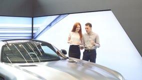 Szczęśliwa para wybiera pierwszy rodzinnego samochód kupować w sala wystawowej zbiory