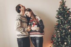 Szczęśliwa para wymienia prezenty i obejmować w eleganckich pulowerach Zdjęcia Royalty Free