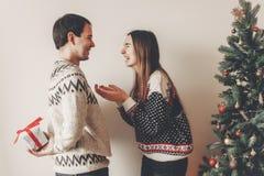 Szczęśliwa para wymienia prezenty w świątecznym roo w eleganckich pulowerach Obraz Stock